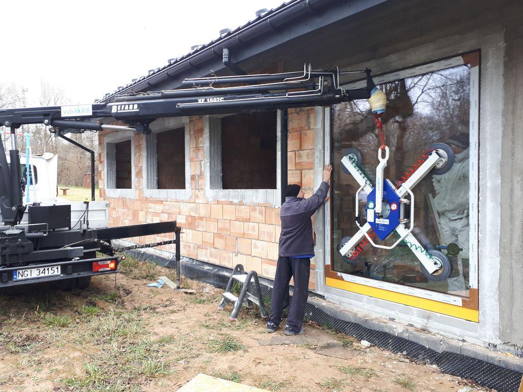 Ustalanie pozycji konstrukcji okiennej w otworze okiennym z użyciem hydraulicznego dźwigu samochodowego i przyssawek firmy Schmalz.