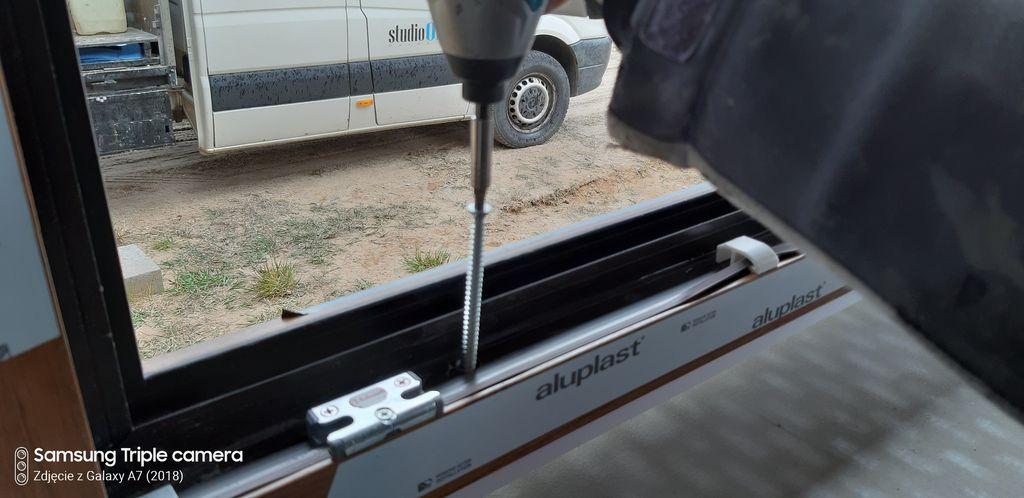 Mocowanie progowego elementu ramy ościeżnicy do muru konstrukcyjnego przy użyciu śrub ramowych.