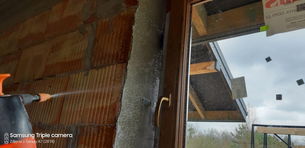 Zwilżanie powierzchni ościeża otworu okiennego w obrębie szczeliny dylatacyjnej przed aplikacją warstwy termoizolacyjnej z pianki PUR.
