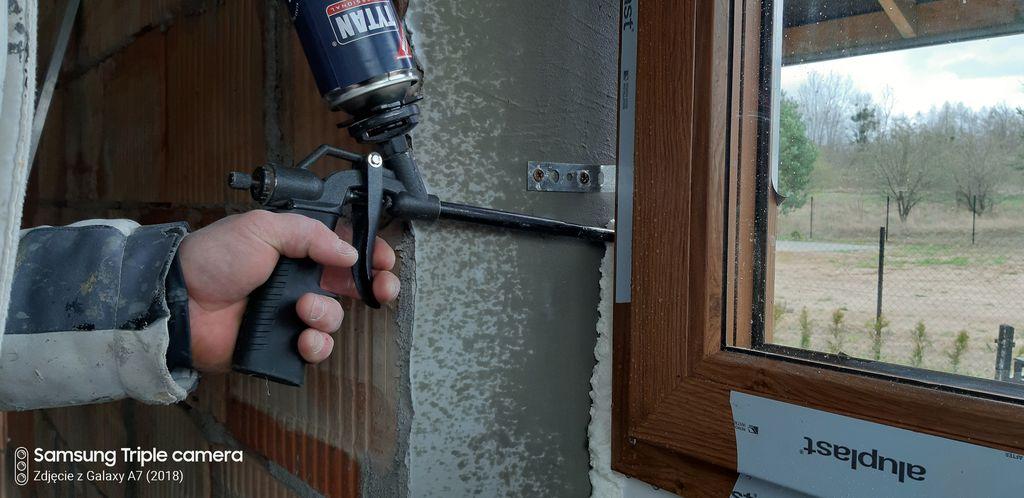 Aplikacja pianki PUR w przestrzeń szczeliny dylatacyjnej powstałej pomiędzy murem konstrukcyjnym, a ramą ościeżnicy okna.