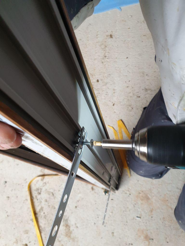 Montaż stalowej kotwy mocującej do ramy ościeżnicy okna.