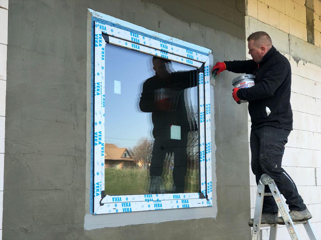 Nakładanie na zewnętrzną powierzchnię połączenia okna z ościeżem polimerowej powłoki uszczelniającej SOUDAL SOUDATIGHT HYBRID