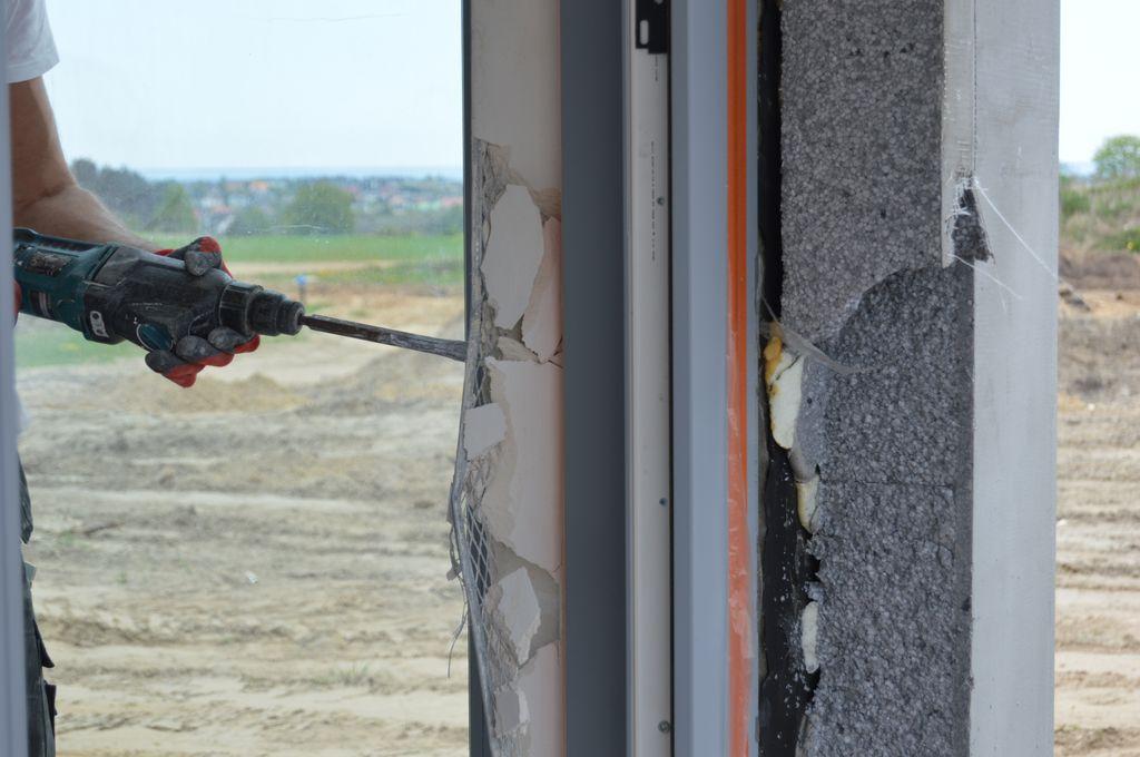 Skuwanie tynków wewnętrznych w celu odsłonięcia punktów mocowania mechanicznego drzwi balkonowych HST