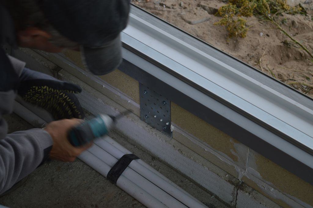 Mocowanie łączników zapobiegających skręcaniu podwaliny pod drzwiami tarasowymi HST