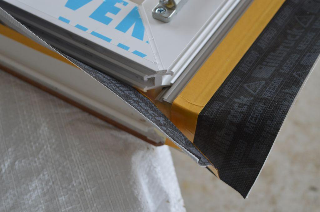 17. Naroże okna z PVC-U wraz z zamocowanymi odcinkami Termo-LISTWY systemu EMO-STROPEX oraz folią uszczelniającą. Detal. Nieosłonięta folią, pusta przestrzeń powstająca pomiędzy listwami schodzącymi się pod kątem prostym, a skośnym narożem ramy ościeżnicy okna