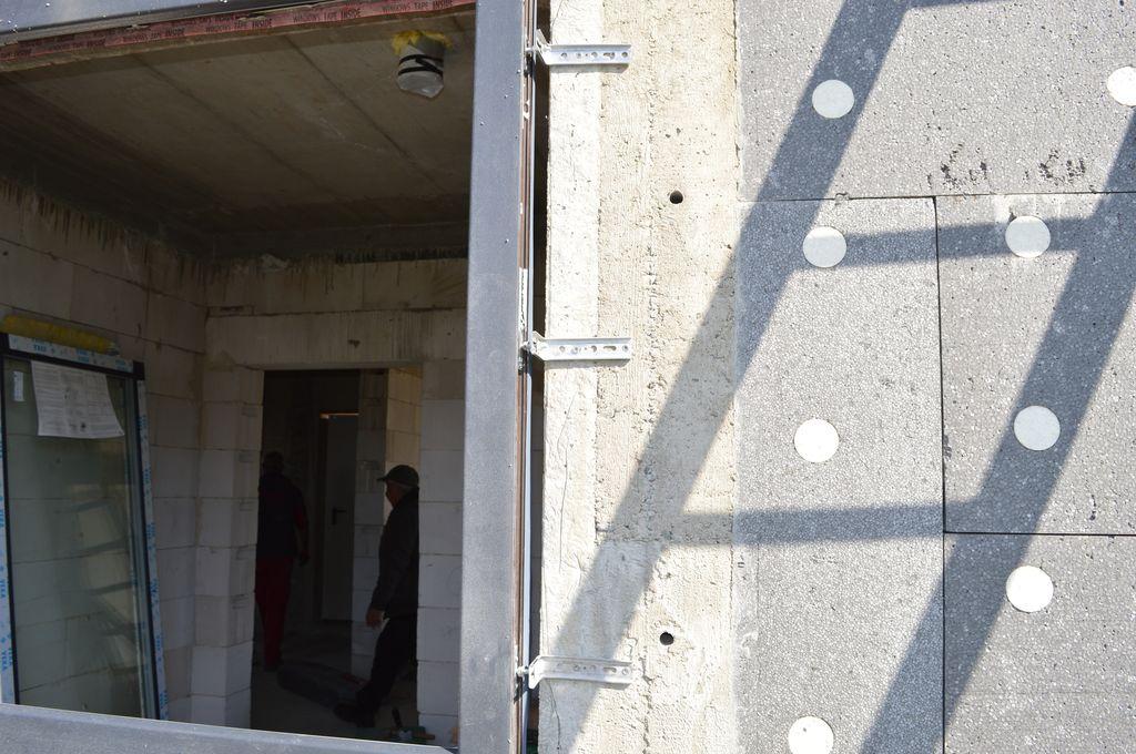 Ościeżnica okna przymocowana do muru konstrukcyjnego przy użyciu wsporników kątowych Knelsen