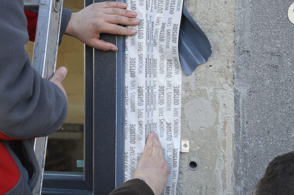 Układanie szerokiej folii paroprzepuszczalnej na połączeniu okna z murem konstrukcji