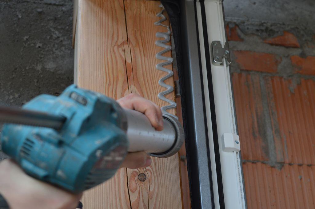 Aplikacja kleju hybrydowego, jako elementu mocowania folii do płaszczyzny drewnianego szkieletu konstrukcji budynku.
