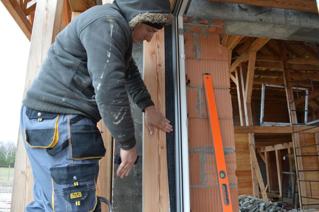 Mocowanie zewnętrznej warstwy izolacji do płaszczyzny drewnianego szkieletu konstrukcji budynku.