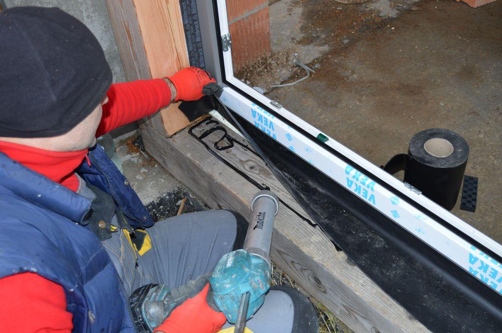 Przygotowanie warstwy mocującej fartuch EPDM do płaszczyzny drewnianego szkieletu konstrukcji budynku.