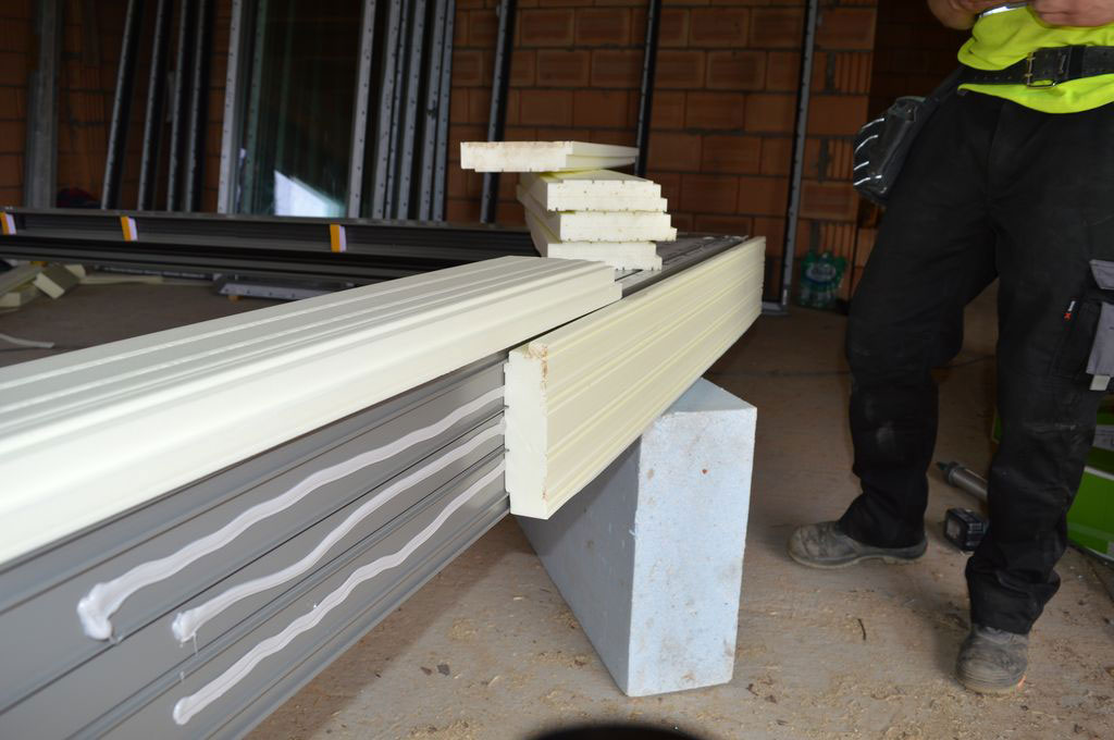 Montaż podwaliny XPS do dolnej płaszczyzny progu aluminiowych drzwi balkonowych HST
