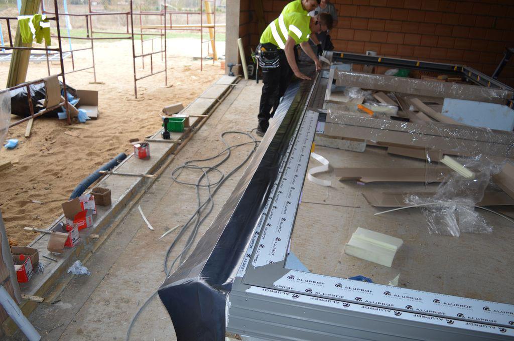 Mocowanie fartucha EPDM do wrębów dolnej części progu aluminiowych drzwi balkonowych HST