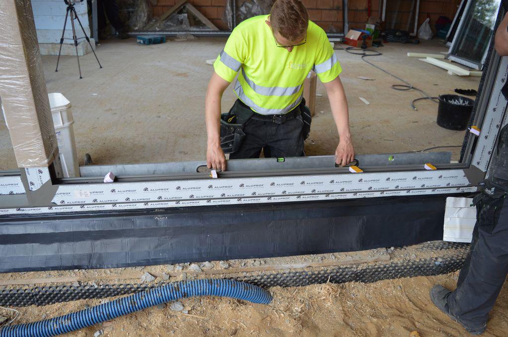 Poziomowanie i ustalanie pozycji konstrukcji aluminiowych drzwi balkonowych HST w otworze ościeża