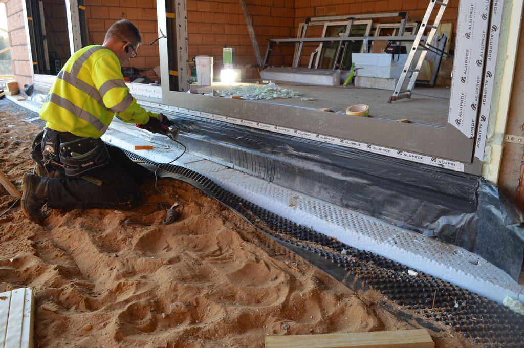 Mocowanie fartucha EPDM, jako zewnętrznej osłony warstwy termoizolacji w obrębie podwaliny i progu aluminiowych drzwi balkonowych HST