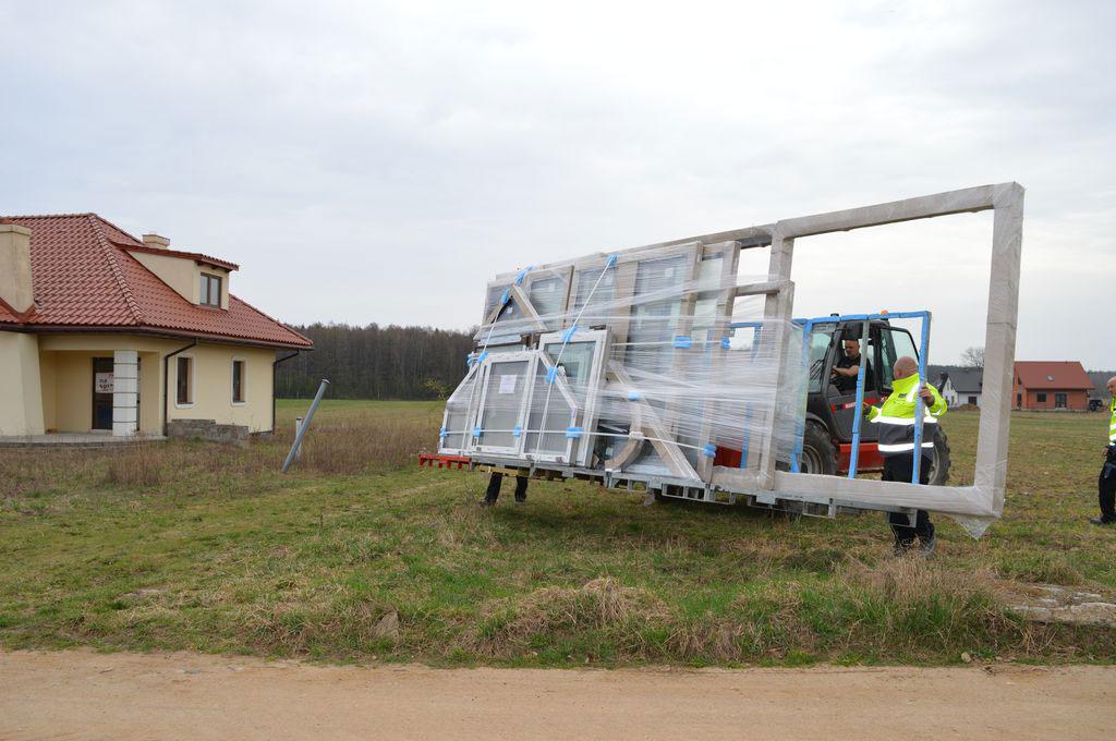 Transport wielkogabarytowych konstrukcji okiennych z miejsca rozładunku na plac budowy
