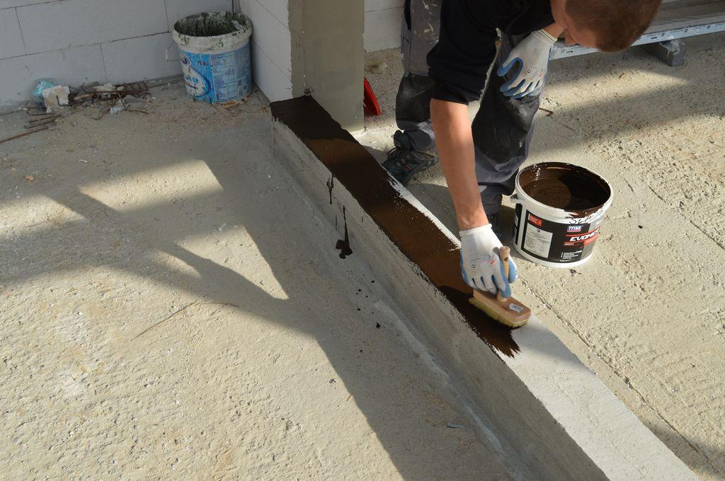 Nakładanie powłoki hydroizolacyjnej na murowany element podwaliny konstrukcji okiennej