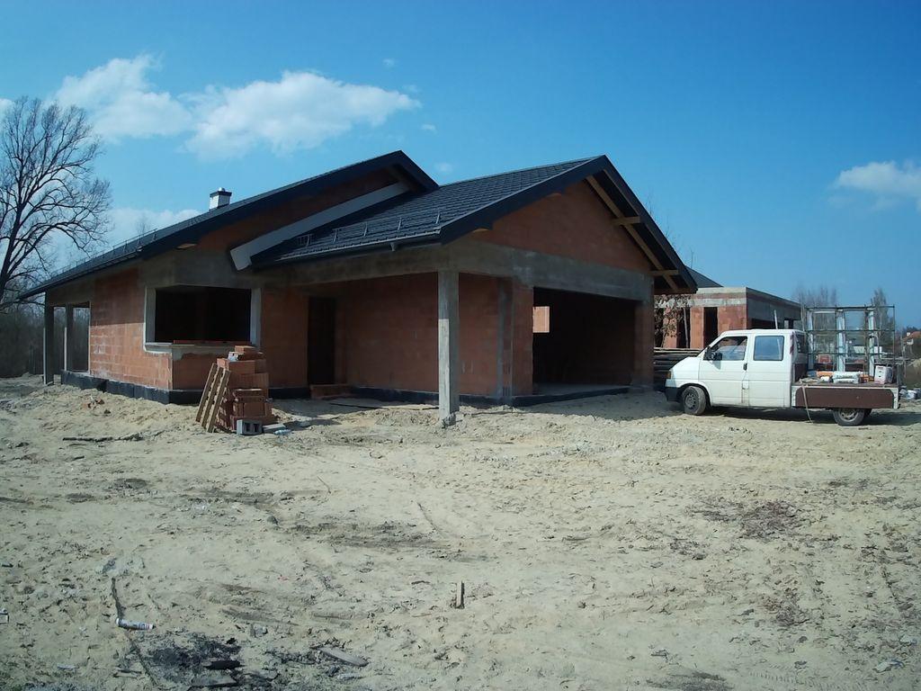 Stan surowy otwarty. Dom jednorodzinny ze ścianami konstrukcyjnymi z pustaków ceramicznych gotowy do montażu okien.