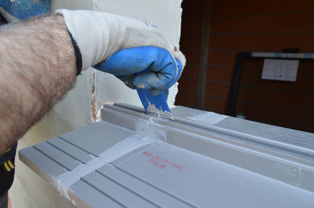 Usuwanie nadmiarów kleju hybrydowego na łączeniu elementów ciepłego parapetu i stopie montażowej w obrębie dodatkowego nacięcia