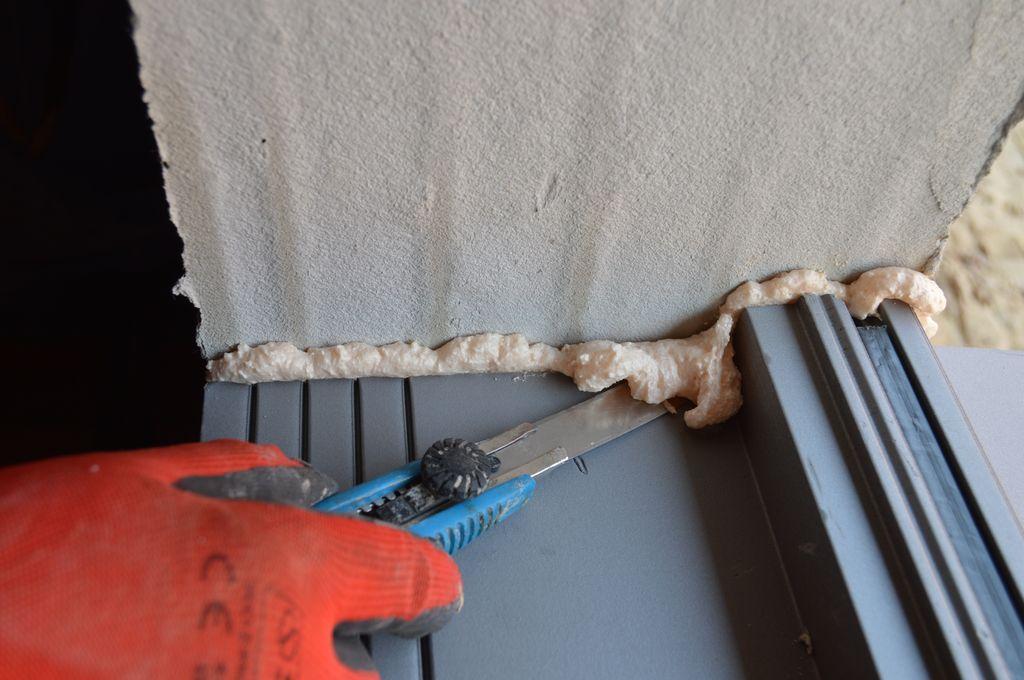 Usuwanie nadmiarów kleju poliuretanowego na styku ciepłego parapetu z murem ościeża