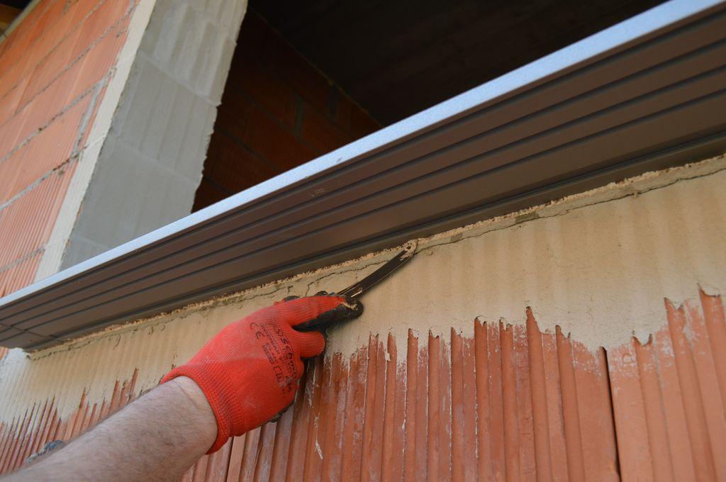 Usuwanie nadmiarów kleju poliuretanowego mocującego ciepły parapet do progu ościeża