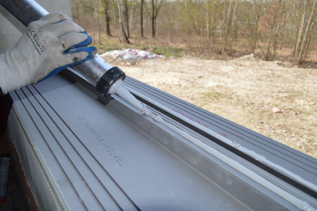 Nakładanie ścieżek kleju hybrydowego wokół wrębu stopy montażowej ciepłego parapetu