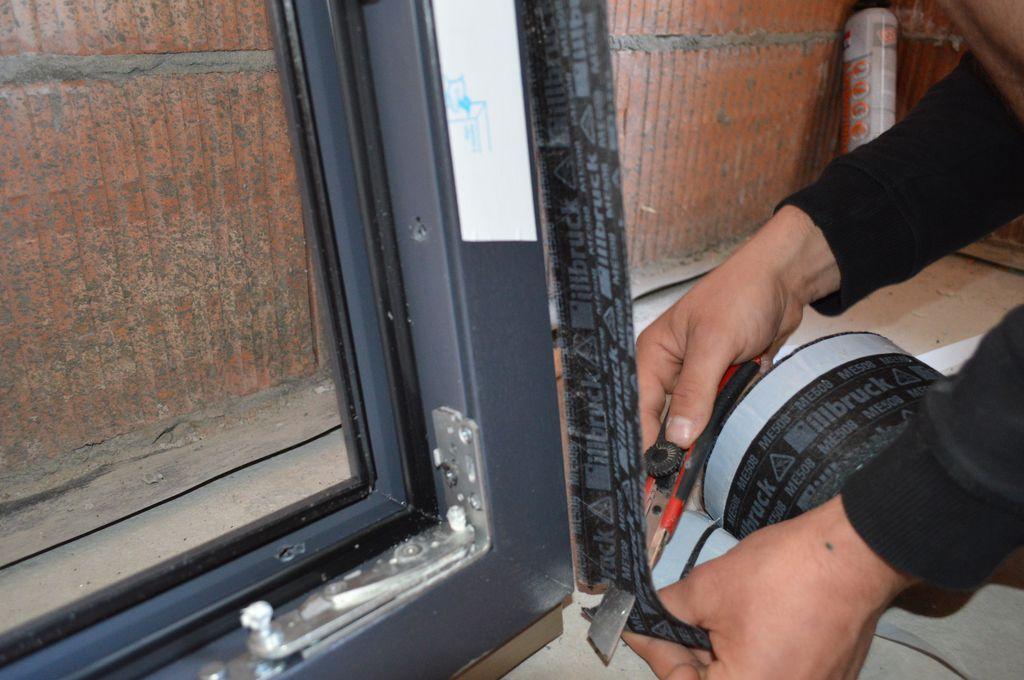 Mocowanie do bocznej płaszczyzny ramy ościeżnicy okna folii paroizolacyjnej stanowiącej wewnętrzną osłonę warstwy termoizolacji