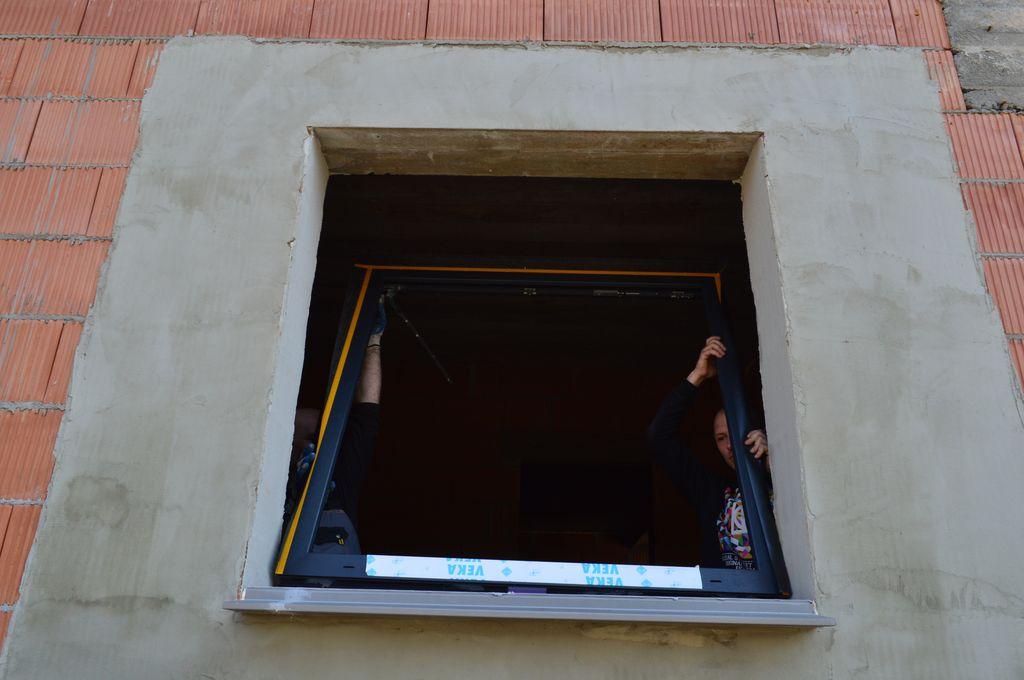 Instalacja i osadzanie ramy ościeżnicy okna na przygotowanej stopie montażowej ciepłego parapetu