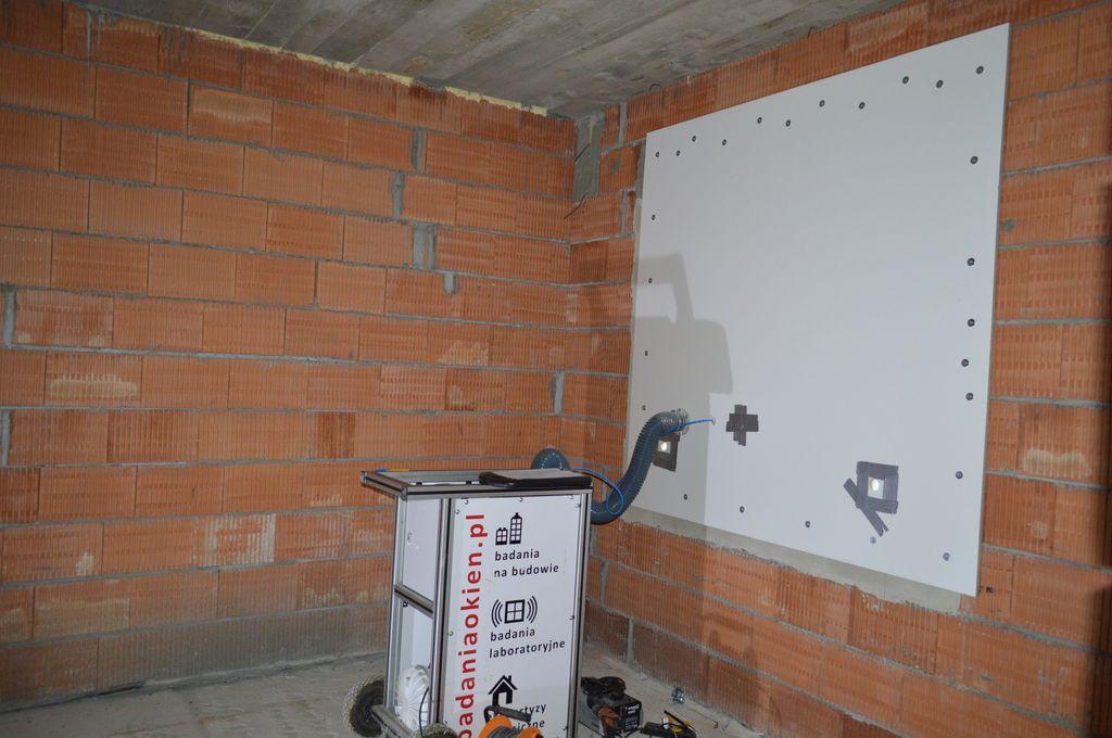 Improwizowana komora ciśnieniowa z podłączonym urządzeniem Windoortester do badania przepływu powietrza przez okna i drzwi balkonowe oraz połączenia montażowe
