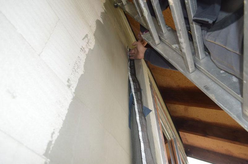 Uszczelnianie wodoszczelną folią paroprzepuszczalną styków połączeń elementów opaski XPS ze ścianą konstrukcyjną.