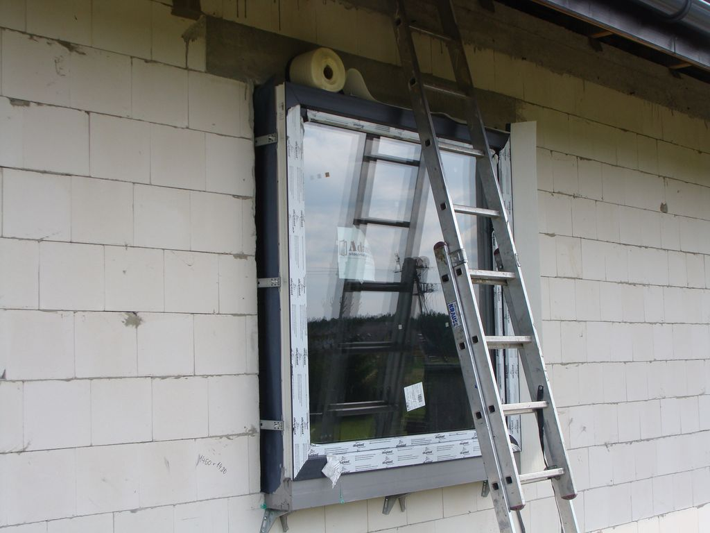 Mocowanie szerokiej folii paroprzepuszczalnej do bocznych płaszczyzn ram ościeżnic okien
