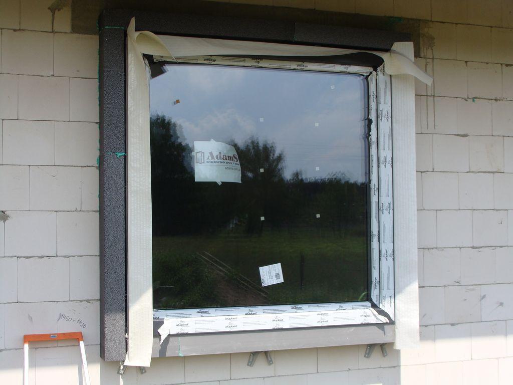 Otwór okienny z oknem osadzonym na kształtce ze styropianu XPS wraz z gotową opaską okalającą i foliami zewnętrznymi okalającą i foliami zewnętrznymi