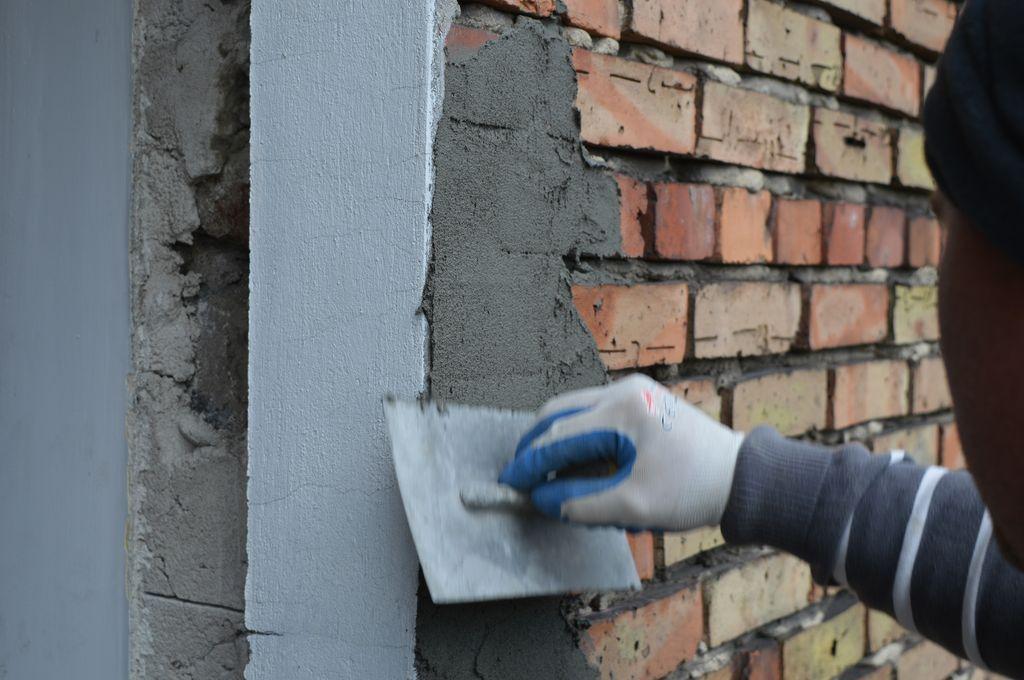 23. Przygotowanie bocznych płaszczyzn ościeża okna w ścianie osłonowej z klinkieru do przyklejania zewnętrznej folii paroprzepuszczalnej.
