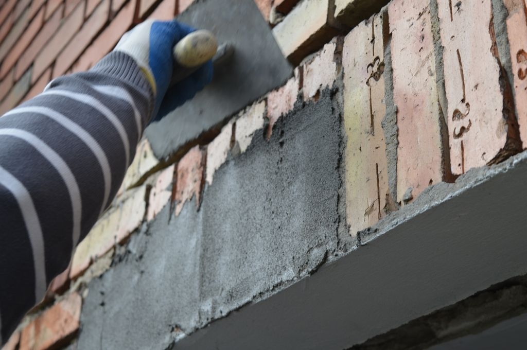 24. Przygotowanie płaszczyzny nadproża ościeża okna w ścianie osłonowej z klinkieru do przyklejania zewnętrznej folii paroprzepuszczalnej.
