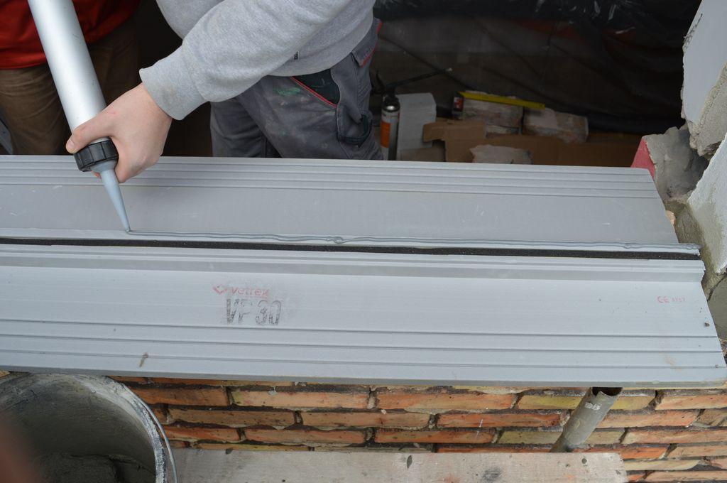 """26. Nakładanie na stopę nośną """"ciepłego parapetu"""" dodatkowej warstwy uszczelniającej połączenie w progu okna."""