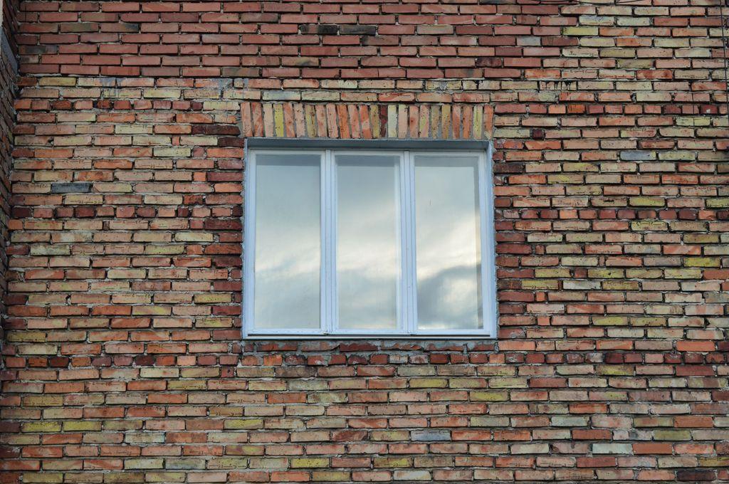 3. Trójdzielne drewniane okno skrzyniowe osadzone za linią węgarka w murze warstwowym 3W widok od strony elewacji.