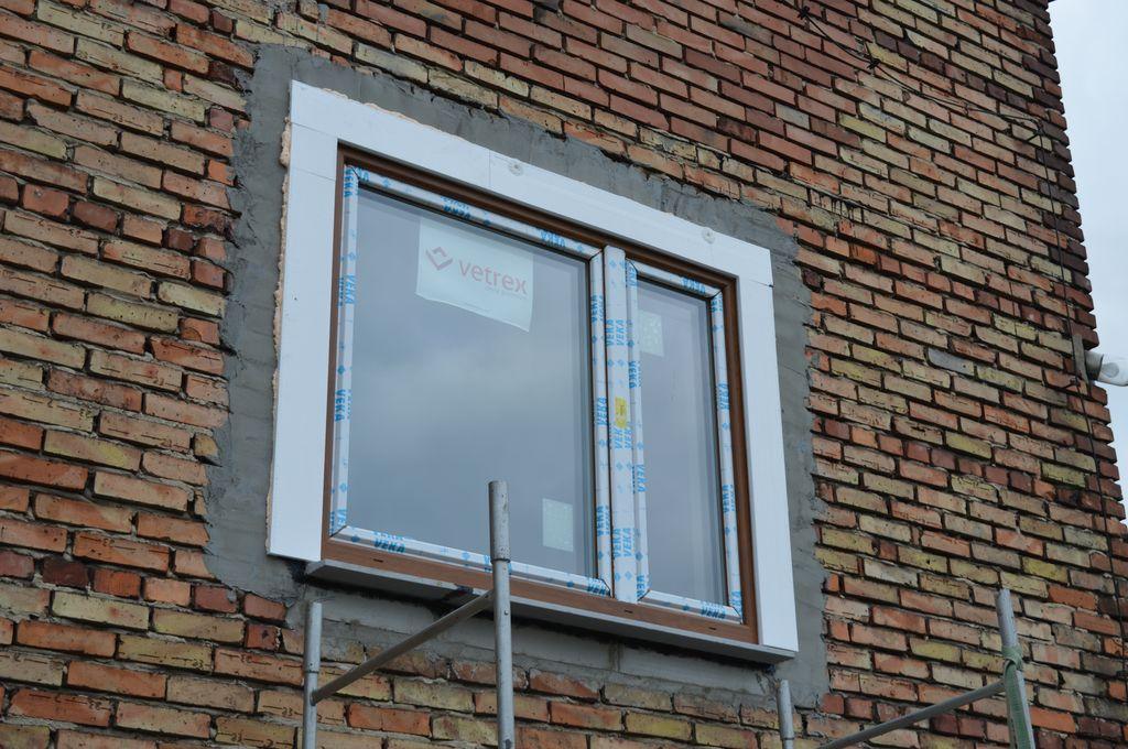 47. Okno PVC zamocowane mechanicznie i prawidłowo zaizolowane w klinkierowej ścianie osłonowej 3W z widoczną styropianową opaską ochronną dla paroprzepuszczalnej folii zewnętrznej.