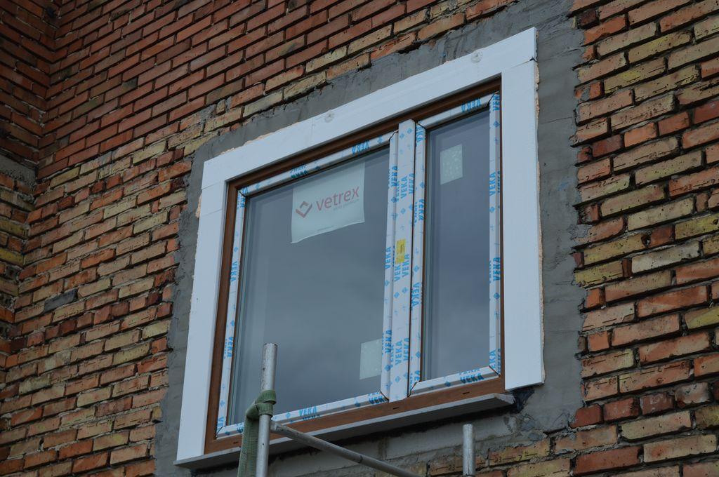 48. Okno PVC zamocowane mechanicznie i prawidłowo zaizolowane w klinkierowej ścianie osłonowej 3W z widoczną styropianową opaską ochronną dla paroprzepuszczalnej folii zewnętrznej.