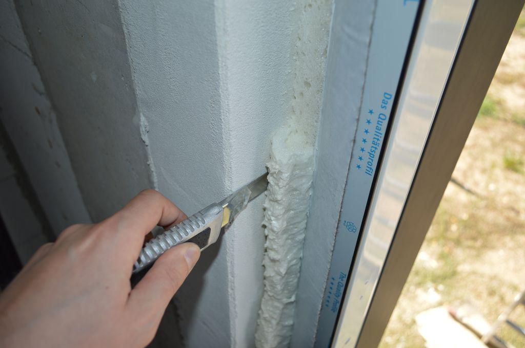 Usuwanie nadmiarów materiału termoizolacyjnego na połączeniu drzwi balkonowych HST z ościeżem