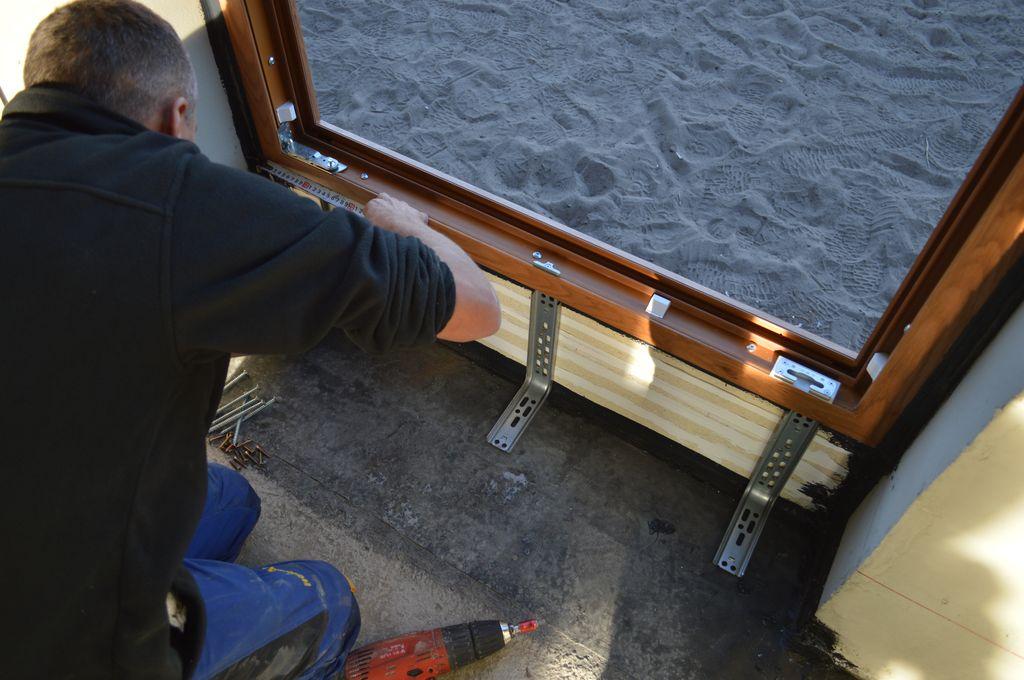 Montaż elementów stabilizujących podwalinę jednoskrzydłowych drzwi balkonowych z PVC