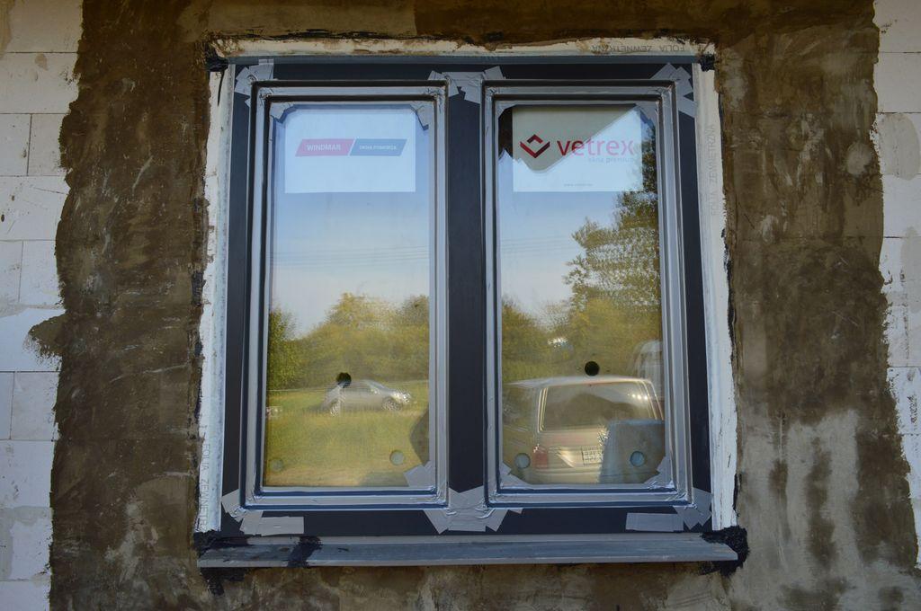 Okno Vetrex V90+ zainstalowane w ościeżu. Wokół okna widoczna opaska z zaprawy wodoszczelnej. Widok od zewnątrz.
