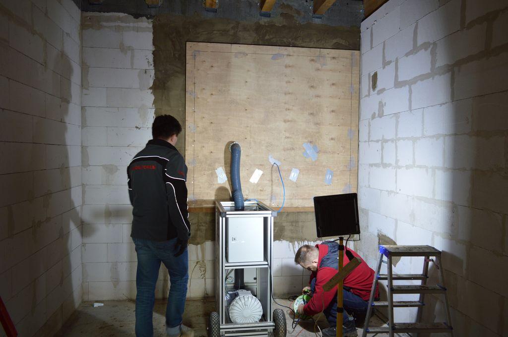 Badania szczelności montażu okien. Podłączanie do improwizowanej komory ciśnieniowej aparatury pomiarowej.