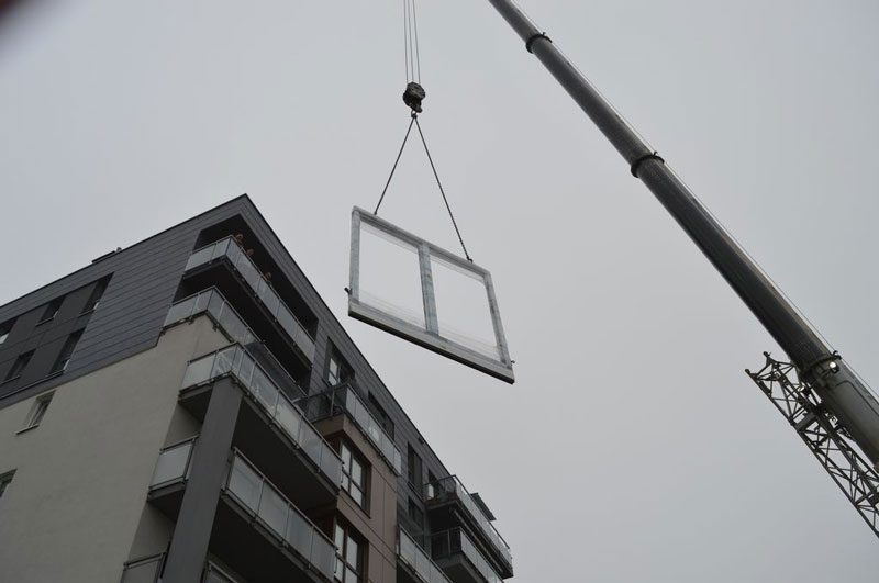 Transport ramy ościeżnicy drzwi balkonowych uchylno-przesuwnych (HKS) na VI piętro wielorodzinnego budynku mieszkalnego