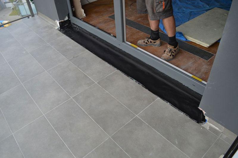 Wykonanie zabezpieczenia zapobiegającego wnikaniu wody opadowej w strefę progu drzwi balkonowych przy użyciu fartucha EPDM
