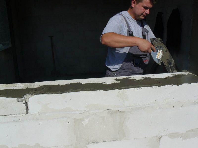 Przygotowanie do montażu ciepłego parapetu. Nakładanie warstwy kleju na powierzchnię progowej części ościeży.