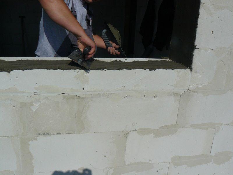 Przygotowanie do montażu ciepłego parapetu. Równomierne rozprowadzenie warstwy kleju na progowej powierzchni ościeży.