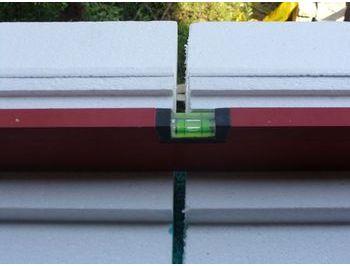 Montaż warstwowy. Ciepły parapet. Sposób poziomowania połączonych i przyklejonych do muru klejem elementów podparapetowego bloku styropianowego.