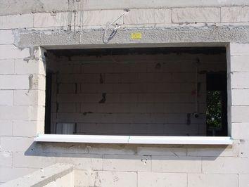 Montaż warstwowy. Tremco illbruck i3. Otwór okienny z zamontowanym podparapetowym blokiem styropianowym. Ciepły parapet, widok ościeży od frontu