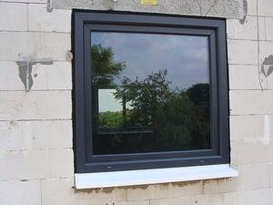 Montaż warstwowy. Tremco illbruck i3. Otwór okienny z gotowym zamontowanym oknem jednodzielnym systemu aluplast ideal 7000 w kolorze grafitowym.