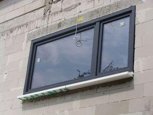 Montaż warstwowy. Tremco illbruck i3. Otwór okienny z gotowym zamontowanym oknem dwudzielnym systemu aluplast ideal 7000 w kolorze grafitowym.