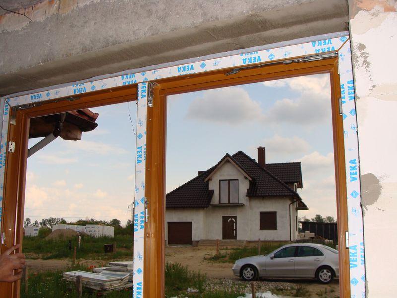 Rama ościeżnicy okna uzbrojona taśmami rozprężnymi ustawiona w otworze okiennym na części nośnej ciepłego parapetu